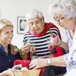 Happy female caretaker looking at senior women choosing wool for knitting at nursing home